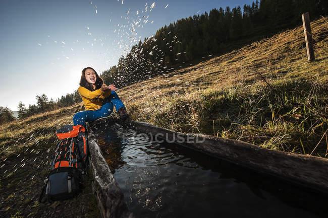 Austria, Altenmarkt-Zauchensee, young woman splashing at watering place — Stock Photo
