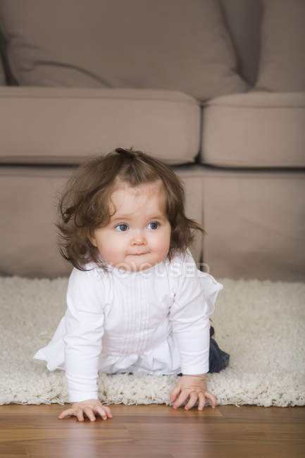 Little girl crawling on carpet — Stock Photo