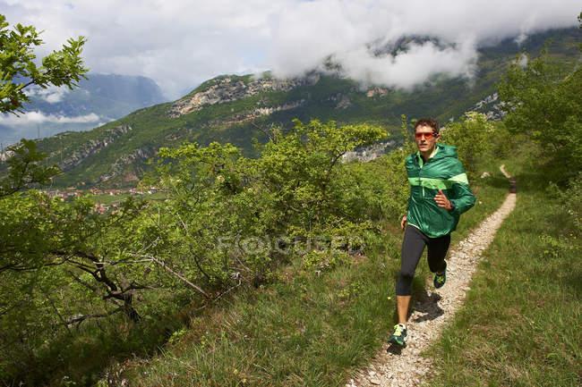 Hombre corriendo cerca del lago de Garda - foto de stock