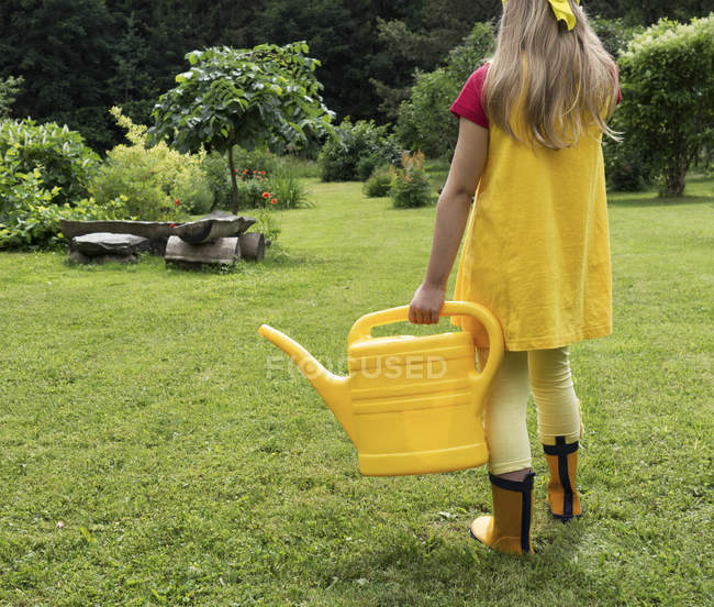 Girl with watering can standing in garden — Stock Photo