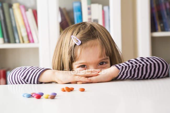 Девочка играет с шоколадными пуговицами — стоковое фото