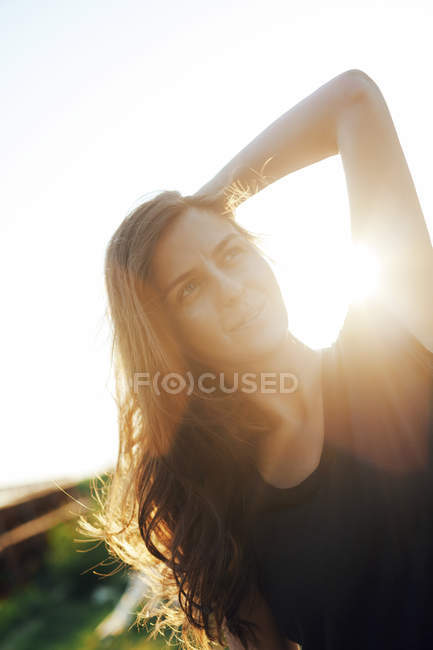 Woman with hand behind her head at backlight — Stock Photo