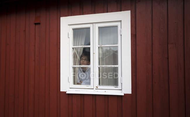 Norwegen, erhaben, Frau schaut durchs Fenster — Stockfoto