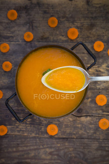 Cooking pot  and spoon of carrot soup and slices — Stock Photo