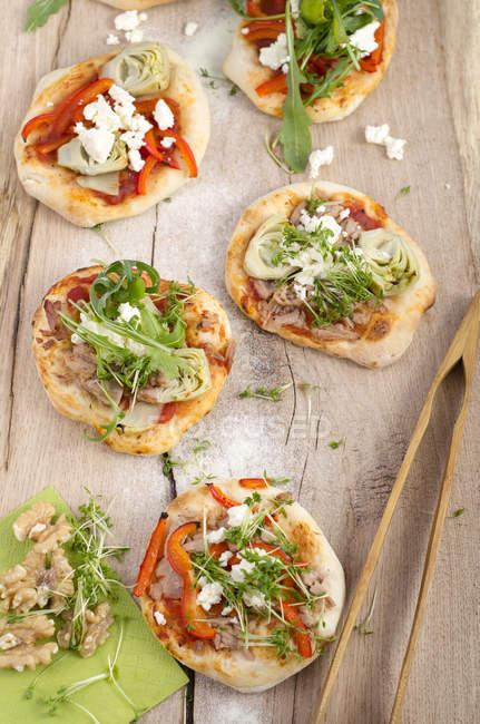 Des mini pizzas avec roquette, fromage de brebis, artickokes, thon et sauce tomate — Photo de stock