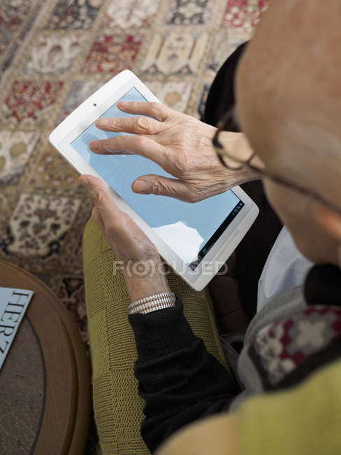 Vieil homme à la maison à l'aide de tablette numérique — Photo de stock