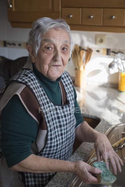 Портрет старшого жінка миття посуду на кухні — стокове фото