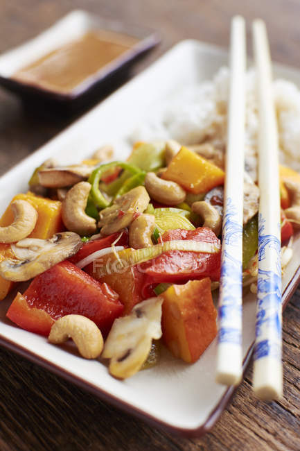 Sweet sour vegetables with pumpkin, mushrooms and cashew nuts on rice — Stock Photo