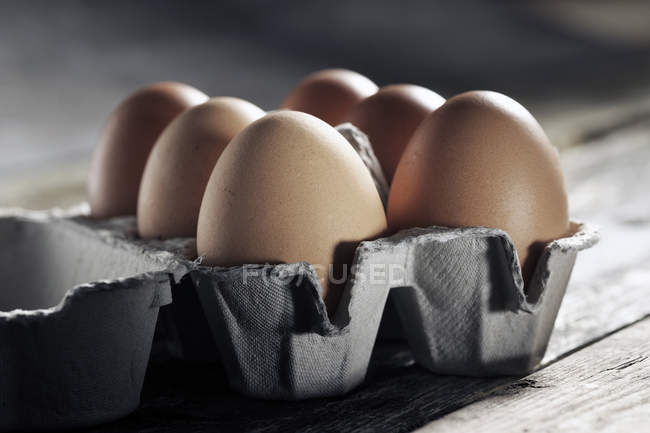 Close-up of Egg box with six brown eggs on wood — Stock Photo