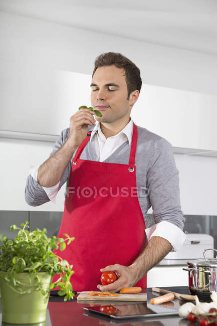 Portrait of man with red apron standing in kitchen smelling basil — Stock Photo