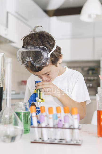 Boy playing science experiments at home looking through