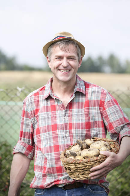 Smiling farmer on organic farm holding basket with potatoes — Stock Photo