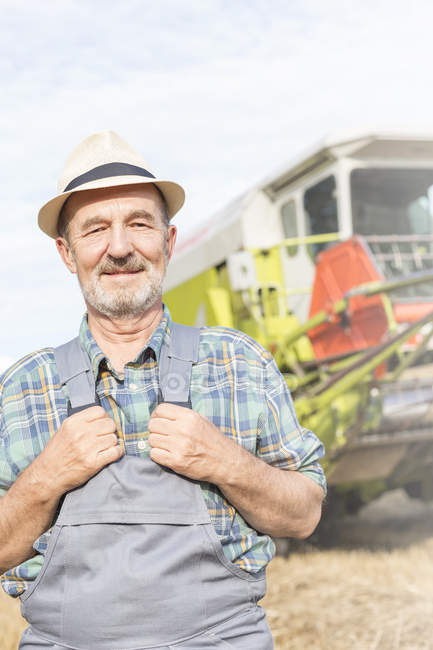 Confident farmer in front of combine harvester — Stock Photo