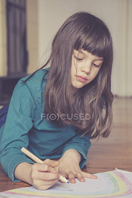 Portrait of girl drawing rainbow on floor — Stock Photo