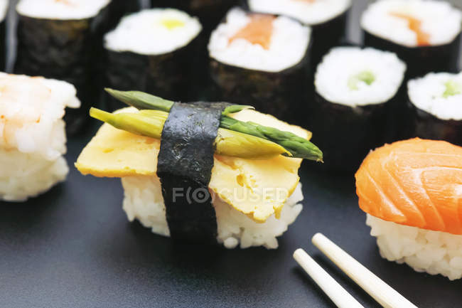 Closeup of variety of sushi with green asparagus served on plate — Stock Photo