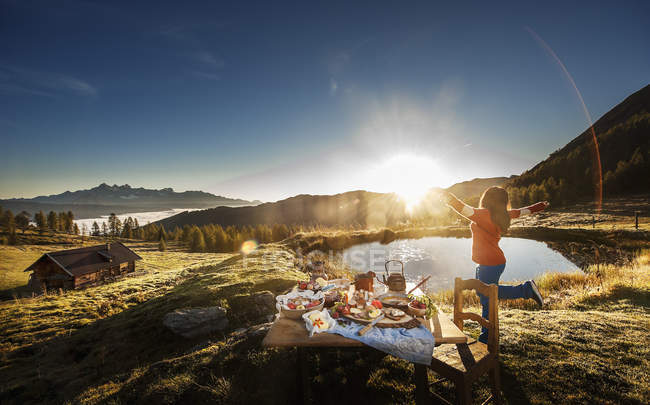 Austria, Salzburg State, Altenmarkt-Zauchensee, woman standing next to breakfast table at sunrise — Stock Photo