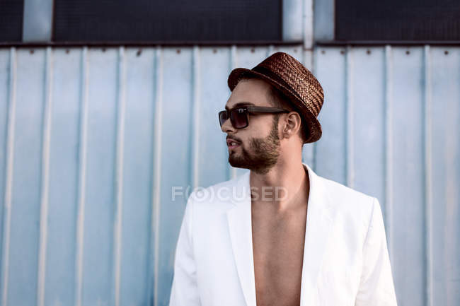 Young man wearing hat, sunglasses and white jacket on bare chest — Stock Photo