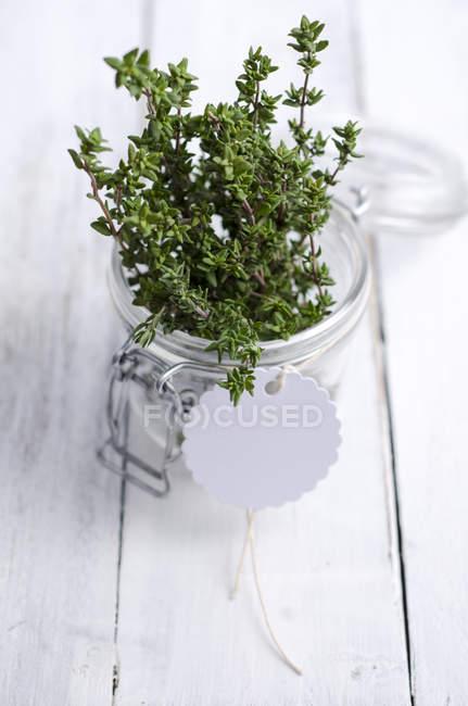 Thym frais dans un bocal de conservation sur la surface en bois — Photo de stock