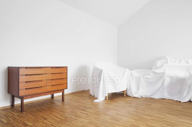 Madia e mobili coperti in un attico — Foto stock