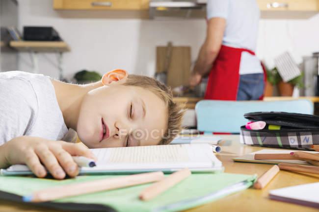 Niño en la mesa de la cocina para dormir en su libro de escuela ...