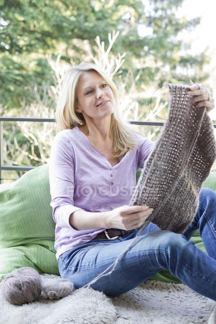 Женщина на балконе с вязанием — стоковое фото