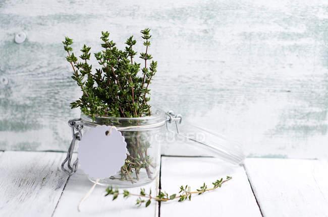 Tomillo fresco en un frasco de conservación sobre una mesa de madera - foto de stock