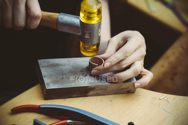 Goldsmith working with rubber mallet on wedding rings — Stock Photo