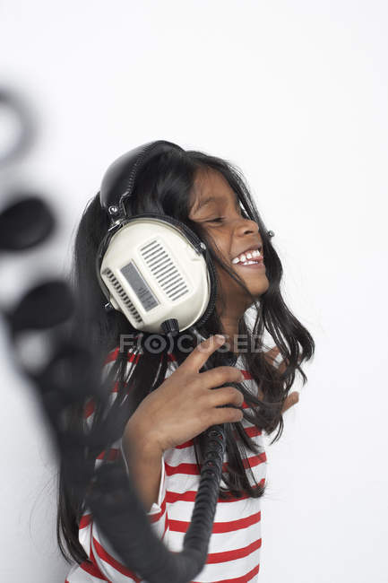 Smiling girl hearing music with headphones — Stock Photo