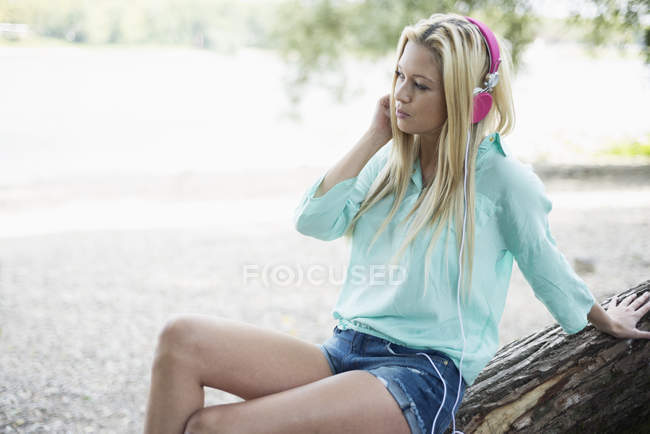 Woman with headphones sitting on tree trunk — Stock Photo