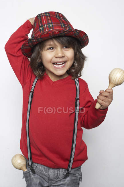 Portrait of smiling little boy with wooden rattle wearing hat and suspenders — Stock Photo