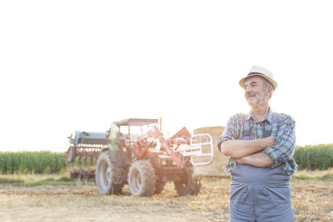 Confident farmer in front of tractor on field — Stock Photo