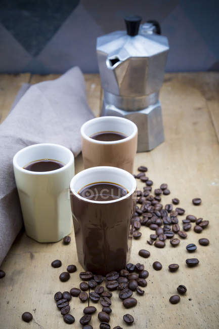 Three cups of coffee, cloth, espresso can and coffee beans — Stock Photo