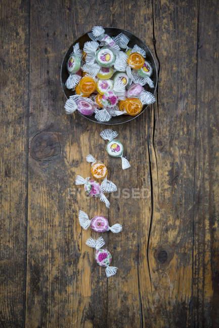 Caramelos en cuenco sobre superficie de madera oscura - foto de stock