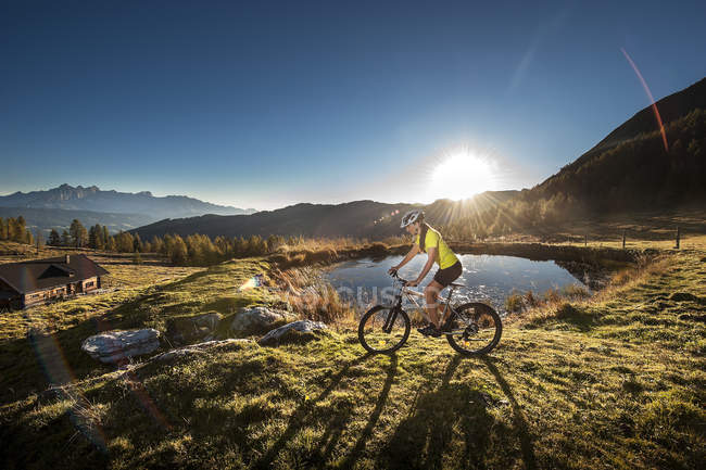 Mountain bike di Austria, Altenmarkt-Zauchensee, giovane donna guida ad alba — Foto stock