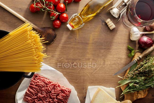 Comida italiana, ingredientes para espaguetis boloñeses sobre madera - foto de stock