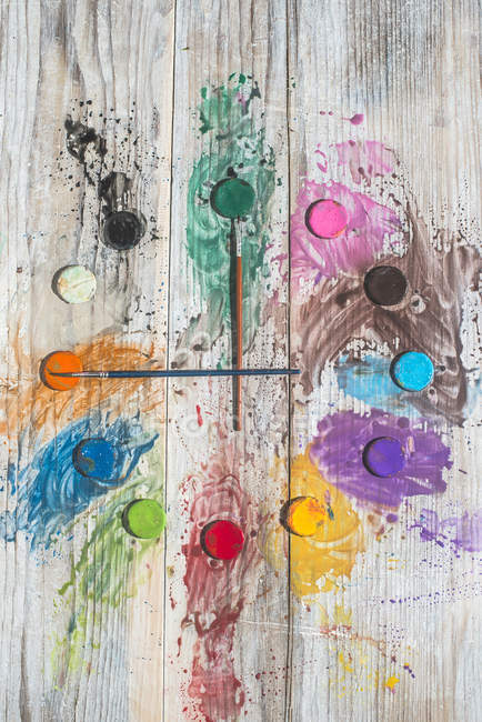 Watercolor paints and brushes forming a clock — Stock Photo