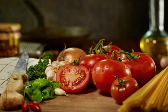 Ingredientes de salsa de tomate vegetal sobre tabla de madera con cuchillo - foto de stock