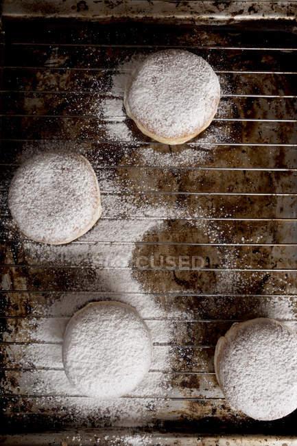 Primer plano de las rosquillas bismarck en la rejilla para hornear - foto de stock