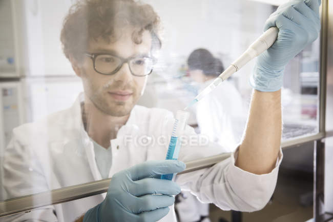 Chercheur dans le laboratoire avec tube à essai et pipette — Photo de stock