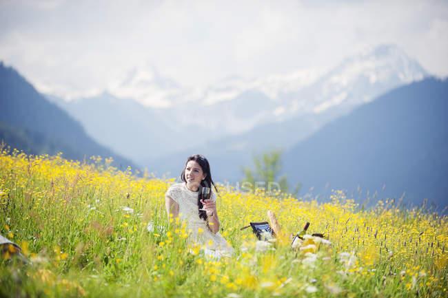 Junge Frau picknickt auf Alm — Stockfoto
