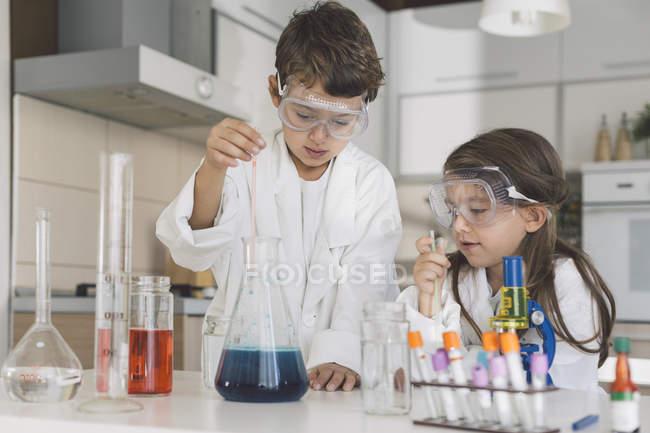 Menino e menina jogando experiências científicas em casa — Fotografia de Stock
