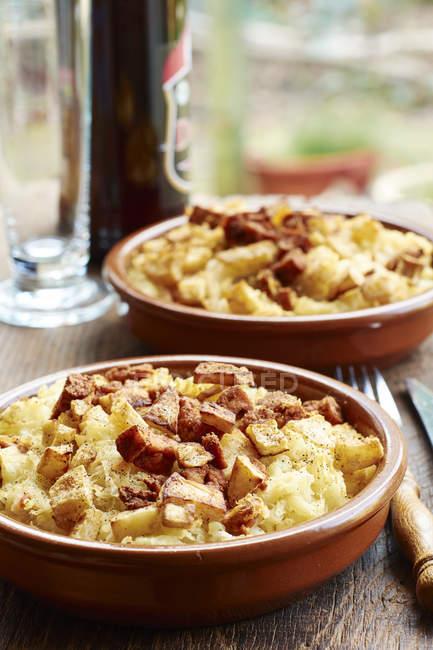Cazuela de puré de patata con crujiente apio de raíz y tofu picante - foto de stock