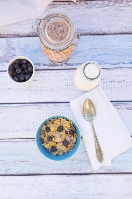 Muesli senza glutine con mirtilli e latte su assi di legno — Foto stock