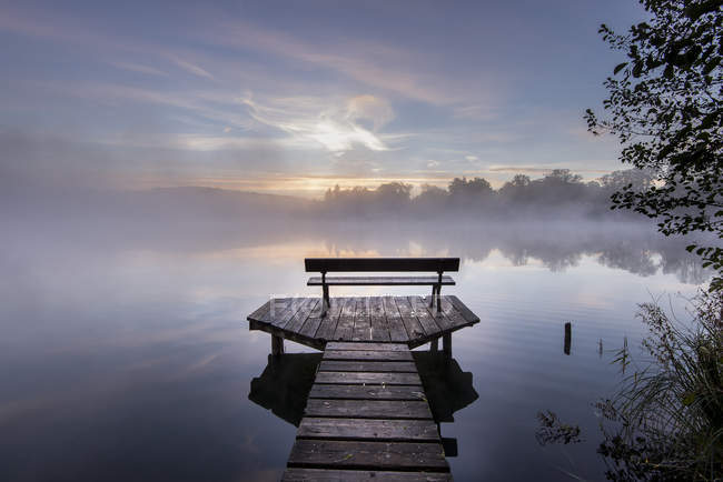 Germany, Bavaria, Wessling, Wesslinger See, boardwalk with wooden bench in the morning mist — Stock Photo