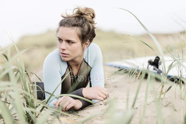 Jeune internaute féminine allongée sur la plage — Photo de stock