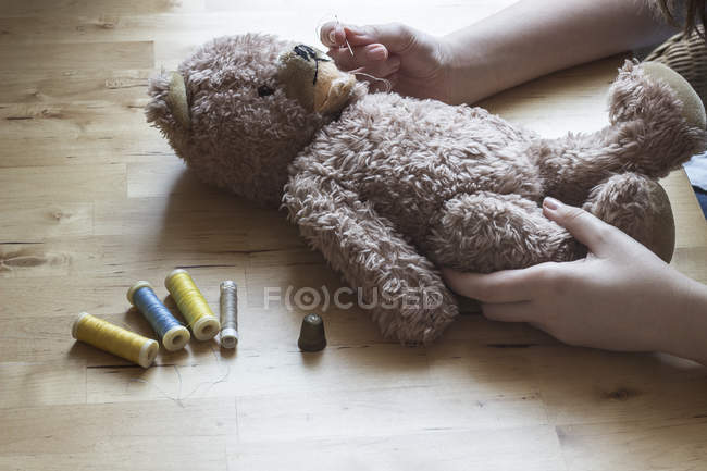 Woman's hands repairing old teddy-bear — Stock Photo