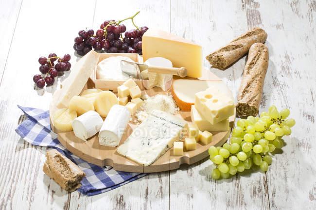 Tabla de quesos con diferentes tipos de quesos, baguette y uvas en madera blanca - foto de stock