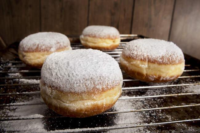 Beignets de Bismarck à glacer le sucre sur la grille de cuisson — Photo de stock