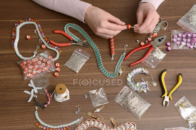 Young woman working on self-made jewelry — Stock Photo