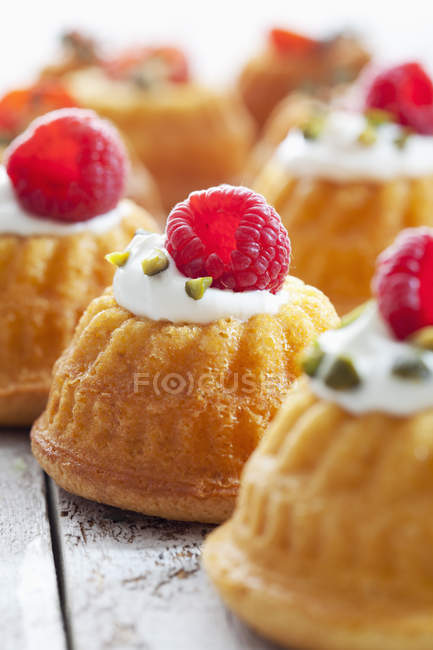 Mini Gugelhupf filled with cream cheese and ricotta garnished with raspberry and pistachio — Stock Photo